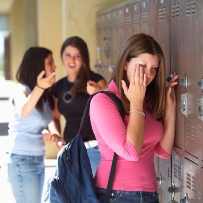 Two teenage girls (15-17) pointing at girl crying beside locker